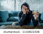 Small photo of drunk alcoholic unemployed man drinking whiskey from the glass and bottle depressed wasted and sad at home couch in alcohol abuse and alcoholism concept