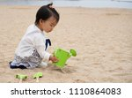 asian baby playing by the beach | Shutterstock . vector #1110864083