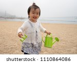 asian baby playing by the beach | Shutterstock . vector #1110864086