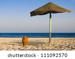 Amphora and an umbrella on the beach with sea in the background - stock photo