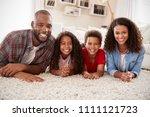 portrait of family lying on rug ... | Shutterstock . vector #1111121723