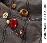 Small photo of Buttons, pins and needles with threads on the background of cotton clothes close up