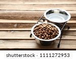 Stock photo cat food and water in bowls on wooden table 1111272953