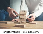 team hands wooden cubes on table | Shutterstock . vector #1111367399