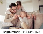 happy young family watching... | Shutterstock . vector #1111390460