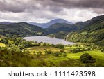 Llyn Gwynant lake nestles in a valley under the wooded slopes of Snowdon and other mountains of Snowdonia in North Wales.