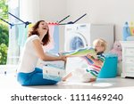 mother and kids in laundry room ... | Shutterstock . vector #1111469240