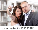 Married couple holding keys to new home - stock photo