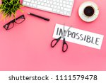 Small photo of Make the impossible possible. Cutting the part im of written word impossible by sciccors. Office desk. Pink background top view copy space