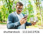 happy man looking on phone with ... | Shutterstock . vector #1111611926