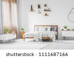 Stock photo wooden shelves with plants above a comfortable double bed in a spacious apartment interior with 1111687166
