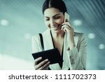 mobile businesswoman using... | Shutterstock . vector #1111702373
