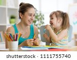 mom helping her child daughter... | Shutterstock . vector #1111755740