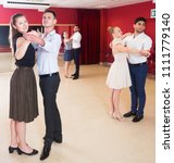 Small photo of Young smiling people learning to dance waltz in dancing class
