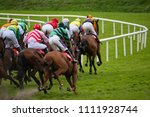 Stock photo view from behind of galloping race horses and jockeys racing down the track 1111928744