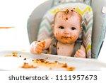 little baby eating her dinner... | Shutterstock . vector #1111957673
