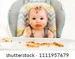 little baby eating her dinner... | Shutterstock . vector #1111957679
