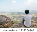 Small photo of Man wear white t-shirts. Sitting in a lonely mood alone. And look out to nature in the foreground. He is thinking, despair Or discouraged. With natural atmosphere around. At the top of the mountain.