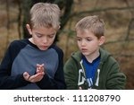 Small photo of Boys observing Smallmouth Salamander, Ambystoma texanum (focus centered on boy with salamander)