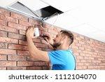 male technician installing... | Shutterstock . vector #1112104070