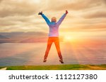 young woman jumping at cliff... | Shutterstock . vector #1112127380