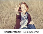 Portrait of red-haired on autumn grass which show hand V symbol. - stock photo