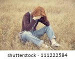 Lonely sad red-haired girl at field - stock photo