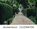 long path lined with tree wall... | Shutterstock . vector #1112306750