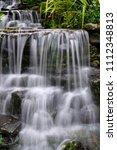 small waterfall in the garden. | Shutterstock . vector #1112348813