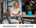 young woman sitting in cafe and ... | Shutterstock . vector #1112386793