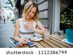 woman using phone in street cafe | Shutterstock . vector #1112386799