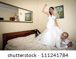 Bride and groom having fun on hotel bed - stock photo