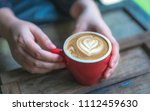 hand holding latte coffee with... | Shutterstock . vector #1112459630