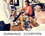 family eating breakfast at a... | Shutterstock . vector #1112491556