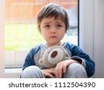sad boy wearing pajamas cuddle... | Shutterstock . vector #1112504390