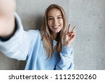Small photo of Picture of young cheerful happy pretty woman standing over grey wall background make selfie by camera showing peace gesture.