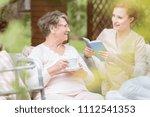 friendly caregiver reading a... | Shutterstock . vector #1112541353