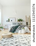 pouf on patterned rug near bed... | Shutterstock . vector #1112545376