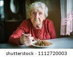 elderly woman eats buckwheat... | Shutterstock . vector #1112720003