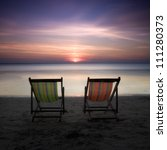 Two colorful chairs in sunset at a perfect beach in the Koh-Chang Island, Thailand