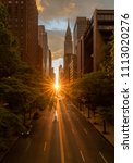 Small photo of Sun setting along the length of 42nd street in New York city known as Manhattanhenge