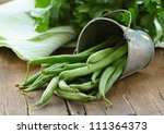 Pods Of Green Peas On A Wooden...