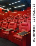 Small photo of Movie theater empty auditorium with red leather comfortable chair with a table. Shooting in difficult conditions with high sensitivity and noise.