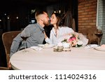 enamored couple sitting in a... | Shutterstock . vector #1114024316
