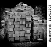 pile of bricks from construction site black and white - stock photo