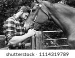 Good looking, hunky cowboy stands next to ranch gate petting and loving his horse - stock photo