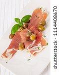 Small photo of Jambon de Parme, olives et basilic sur une plaque blanche et un fond en bois blanc. Verticalement.