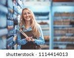 smiling seller in uniform in... | Shutterstock . vector #1114414013