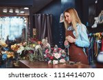 young florist with a bouquet in ... | Shutterstock . vector #1114414070
