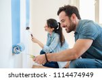 young couple painting walls in... | Shutterstock . vector #1114474949